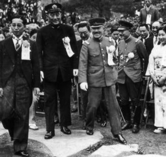 Seishirō Itagaki - The newly appointed War Minister Itagaki (center, stepping down from the rock) with his vice-minister Hideki Tōjō (right) and Navy minister Mitsumasa Yonai (left, in black Navy uniform, standing on the rock)