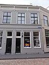 foto van Huis met gebosseerd gepleisterde gevel met kroonlijst op consoles die voortzetting is van die van nr 66