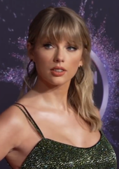 Medium shot of Swift in dress with little sequins, in front of AMA backdrop