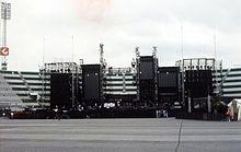 Une scène de concert élaborée, vue pendant la journée dans un stade vide.  La scène comprend plusieurs structures rectangulaires sombres.