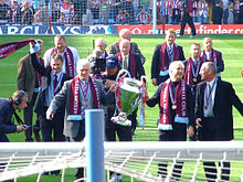 In the foreground is two men holding a large cup, they have claret scarves and a medal around their necks. Around them are ten old players in suits with medals and scarves around their necks