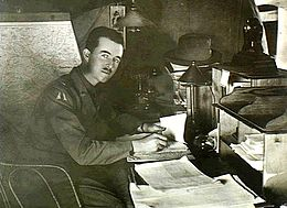Man in military uniform looking up from a desk covered in papers