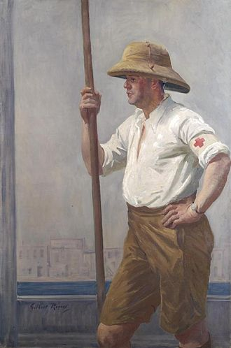 British Red Cross - A three quarter length portrait of a Red Cross and Order of St John barge orderly, wearing sandy coloured shorts, pith helmet and white shirt. He stands side on and holds a wooden barge pole in his right hand. He appears to be standing on the deck of a boat, with the River Tigris and buildings on the riverbank visible behind him, 1919