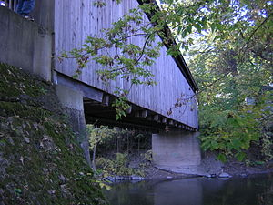 Ada Covered Bridge - Underside view, showing truss ends protruding from the sheathing.