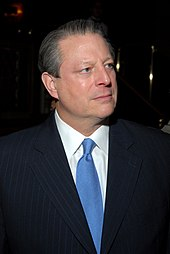 A man wearing a black suit with a blue tie