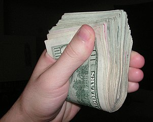 Hand holding a wad of cash