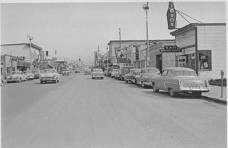 Anchorage Times - Fourth Avenue in Anchorage in 1953, looking east from near I Street.  The offices of the Times are several buildings down on the right.  The Times would remain in that location until its closing, greatly expanding its offices and plant during the 1970s.  That latter building stands today as the administrative headquarters of the Alaska Court System.
