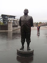 A bronze-statued Herbert Chapman, standing with hands behind his back. The statue was erected to commemorate his time at Arsenal.