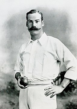 Mold standing wearing cricket whites and holding a cricket ball in his right hand
