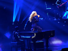 A woman kneeling upon a piano whilst singing