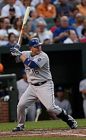 A man in a grey baseball uniform with a blue helmet holds a baseball bat while preparing for a pitcher to throw the ball to him.