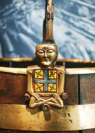 "Oseberg Ship - The so-called ""Buddha bucket"" (Buddha-bøtte), a brass and cloisonné enamel ornament of a bucket (pail) handle in the shape of a figure sitting with crossed legs."