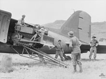 A tiny bulldozer emerges from the rear door of an aircraft onto a grass airstrip. Three men stand around watching.