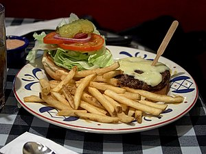 History of the hamburger - Open hamburger with cheese and fries served in an American diner.