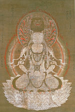 Frontal view of a deity seated on a pedestal.