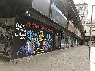 """Un murale dipinto su un muro in una strada a Girona, Spagna: il trofeo dell'Eurovision appare coperto di filo spinato circondato da palazzoni, con le parole """"# BoycottEurovision2019"""" sopra e """"Palestina libera"""" in inglese e arabo in alto a sinistra"""