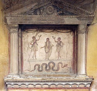 Lares - Lararium at the House of the Vettii: Two Lares, each holding a rhyton, flank an ancestor-genius holding a libation bowl and incense box, his head covered as if for sacrifice. The snake, associated with the land's fertility and thus prosperity, approaches a low, laden altar. The shrine's tympanum shows a patera, ox-skull and sacrificial knife.