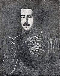 Lithograph depicting a dark-haired man with moustache wearing a heavily embroidered military tunic with epaulettes, sash of office and several medals and orders at his neck