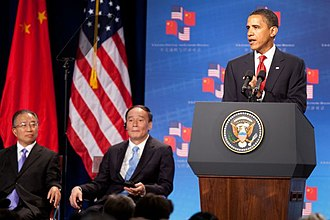 2009 in China - President Barack Obama addresses the opening session of the first U.S.–China Strategic and Economic Dialogue at the Ronald Reagan Building and International Trade Center in Washington, Monday, July 27, 2009. Listening at left are Chinese Vice Premier Wang Qishan, center, and Chinese State Councilor Dai Bingguo, left.