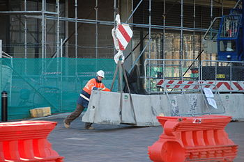 Construction worker moving a concrete barrier.