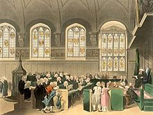 A courtroom seen from the side. Made of stone, there is a large, arched ceiling and four stained glass windows. There is a single wigged judge, assisted by a bench of clerks in front of him. In front of the clerks sit two rows of barristers, in black gowns and curled white wigs.