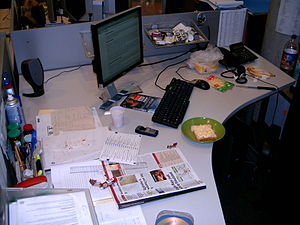 Desk - An office desk in a cubicle, which shows the sharing of space between computer components and paper documents.