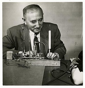 David Wechsler - View of Dr. David Wechsler seated at a table, conducting some sort of test on a patient.