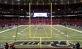 Фотография футбольного поля, сделанная из зачетной зоны, со стойками ворот на переднем плане.