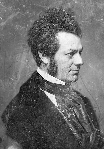 Scratched black and white photo of Edwin Forrest in profile intently looking out ahead. His dark hair is longer on top and slightly wild. He wears mutton-chop facial hair. He wears a dark jacket, starched white color, and voluminous dark patterned necktie that cascades down his breast.