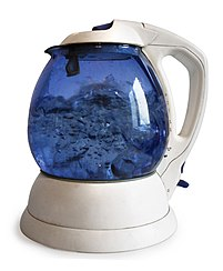 picture of electric kettle with a glass carafe perched on its electric base showing boiling water