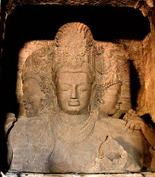 A brownish stone three-headed statue carved with ornaments