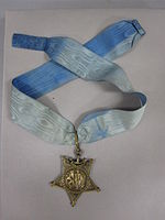 Star-shaped medal on a blue neck ribbon