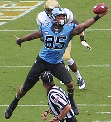 An American football player catching a football in mid-air.