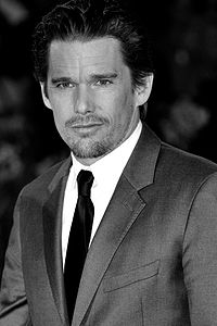 A caucasian male with dark slick hair, wearing a two-piece grey suit, with a white shirt and black tie.