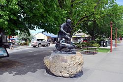"A cast sculpture mounted on a boulder. The sculpture depicts a long haired and bearded man, dressed in a shirt and trousers and carrying a staff. By his side is a sheep dog. Both the man and the dog are facing right. A brass plaque is on the boulder reading ""James MacKenzie & dog:Statue by Sam Mahon:Unveiled 7 November 2003"". Behind the statue is a paved and treed area with small square patches of grass. A small service road is to the left of the statue, flanked by parked cars and shops."