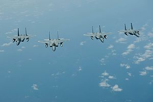 Four F-15C Eagles fly in formation off the coast of Japan (25896707120).jpg