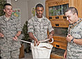 From left, U.S. Air Force Airman 1st Class Allen Airoldi holds a burlap sack so Airman 1st Class Lennell Day can safely put a Great Plains rat snake into it as Airman 1st Class Ponce Carrillo, holding a ball 110725-F-NS900-003.jpg