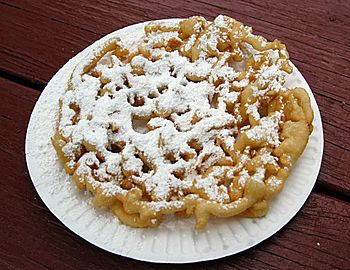 English: A funnel cake covered in powdered sugar.