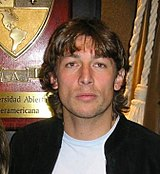 A photograph of a man with medium-length brown hair wearing a black jacket over a white shirt.