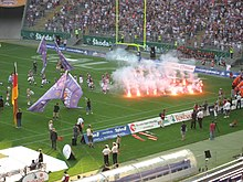 Players run by flares on the field