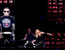 A blond woman sitting on a stage on her knees, flanked by an African-American man on her right, in the same position. They are both dressed in black pants and vests, with broad rubber bands on their hand. To their right, a vertical rectangular screen shows a man in a black t-shirt standing with his hands on his waist and wearing sunglasses.