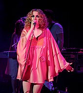 A woman with blonde curly hair wearing a pink dress and singing into a microphone