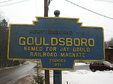 "A blue sign with gold border reading ""NEWFOUNDLAND - 9/GOULDSBORO/NAMED FOR JAY GOULD/RAILROAD MAGNATE/FOUNDED/1871"" in gold lettering, with a snowy scene in the background."