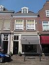 foto van Huis met schilddak en zeer eenvoudige lijstgevel; latere winkelpui