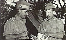 Two men in military uniform conferring in front of a tent. The one on the right is holding a stack of papers.