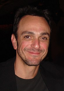 Head shot of broadly smiling man in black with receding dark hair and a day's beard growth on his face.