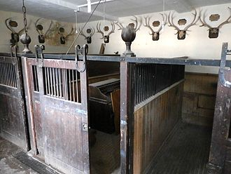 Devon and Somerset Staghounds - Loose boxes in stable block built by Sir Thomas Dyke Acland, 9th Baronet (1752–1794) at Holnicote, with his stag head trophies