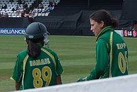 Two female in green cricket uniforms with yellow piping are talking. The left-hand female is wearing a helmet and has dark skin, 'ISMAIL' and '89' are visible in yellow writing on her back. The right-hand female has 'KAPP' and '06' visible on her back.