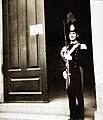 Italian national policeman on guard outside an Allied military government office, Sicily, 1943 (23933646594).jpg