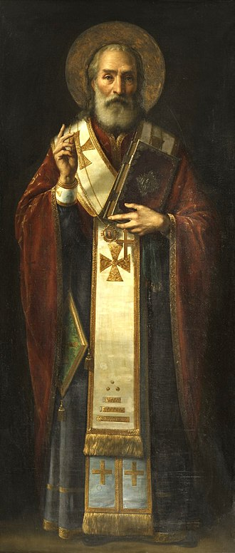 Saint Nicholas - Full-length icon of Saint Nicholas by Jaroslav Čermák, showing him with a halo, dressed in clerical garb, and holding a book of the scriptures in his left hand while making the hand gesture for the sign of the cross with his right.